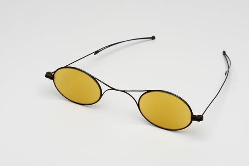 orenbril met knikveer, stalen montuur en geel getinte glazen