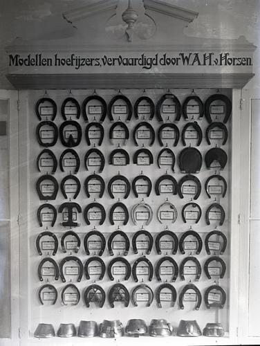 Opname van een wandbord met de tekst 'Modellen hoefijzers, vervaardigd door W.A.H. van Horsen.'